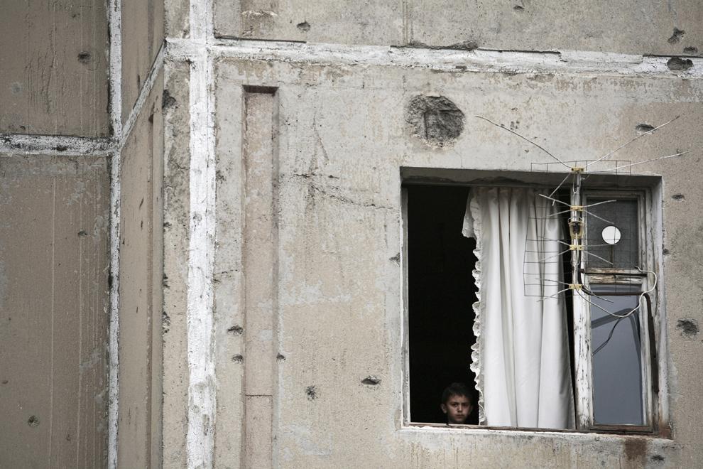 Un copil priveşte de la geamul unui apartament ce are pereţii exteriori atinşi de gloanţe, în Khojaly, Nagorno-Karabah, vineri, 19 septembrie 2008. Khojaly este un oras din Nagorno-Karabah si este situat la 10 km nord-est de capitala Stepanakert.