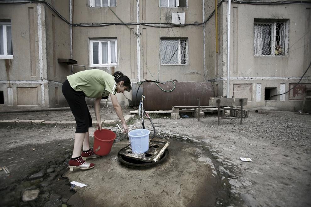 O femeie umple găleţi de plastic cu apă în faţa unui bloc de apartamente avariat în timpul războiului, în oraşul Khojaly, vineri, 19 septembrie 2008.