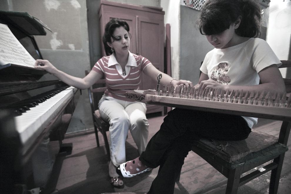 Profesoara Nona Valerigna (33 de ani) o învaţă pe eleva sa, Bella Gasparyan (10 ani) să cânte la kanun, în timpul unei ore de muzică la Şcoala de Muzică Khmoitas, din Stepanakert, sâmbătă 20 septembrie 2008, în Nagorno-Karabah. Cu o populaţie de 140,000, majoritatea fiind armeni, Republica Nagorno-Karabah îşi caută stabilitatea economică şi politică. Rata mare de şomaj, salariile mici şi lipsa oportunităţilor pentru tineri fac din republica nerecunoscută un loc în care se trăieşte greu.