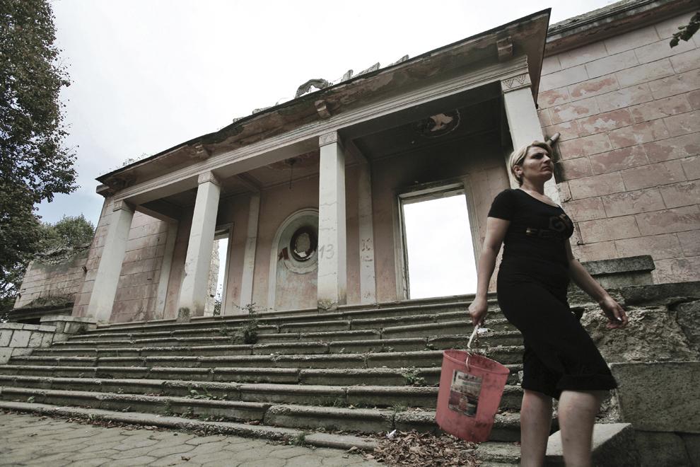 O femeie trece prin faţa unei cladiri comuniste în ruină, în oraşul Shushi, joi, 18 septembrie 2008. Înaintea izbucnirii războiului, oraşul Shushi, al doilea ca mărime din Nagorno-Karabah ca mărime şi densitate a populaţiei, era centrul cultural al regiunii.