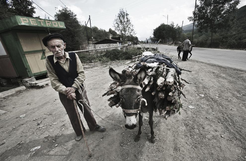 Un bătrân cară lemne cu ajutorul măgarului său pe o stradă din satul Vank, regiunea Martakert, Nagorno-Karabah, sâmbătă, 20 septembrie 2008. Cu o populaţie de 140,000, majoritatea fiind armeni, Republica Nagorno-Karabah îşi caută stabilitatea economică şi politică. Rata mare de şomaj, salariile mici şi lipsa oportunităţilor pentru tineri fac din republica nerecunoscută un loc în care se trăieşte greu.