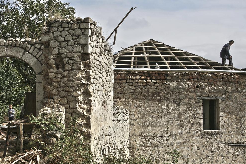 Un bărbat lucrează la reabilitarea unei case din oraşul Shushi, Nagorno-Karabah, joi, 18 septembrie 2008. Înaintea izbucnirii războiului, oraşul Shushi, al doilea ca mărime din Nagorno-Karabah ca mărime şi densitate a populaţiei, era centrul cultural al regiunii.