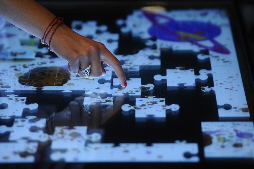 O tânără rezolvă un puzzle pe o masă multi-touchscreen, în timpul festivalului dedicat industriei digitale şi interactive din Europa Centrală şi de Est, Interactive Central and Eastern Europe Festival 2014 (ICEEFest), în Bucureşti, joi, 12 iunie 2014.