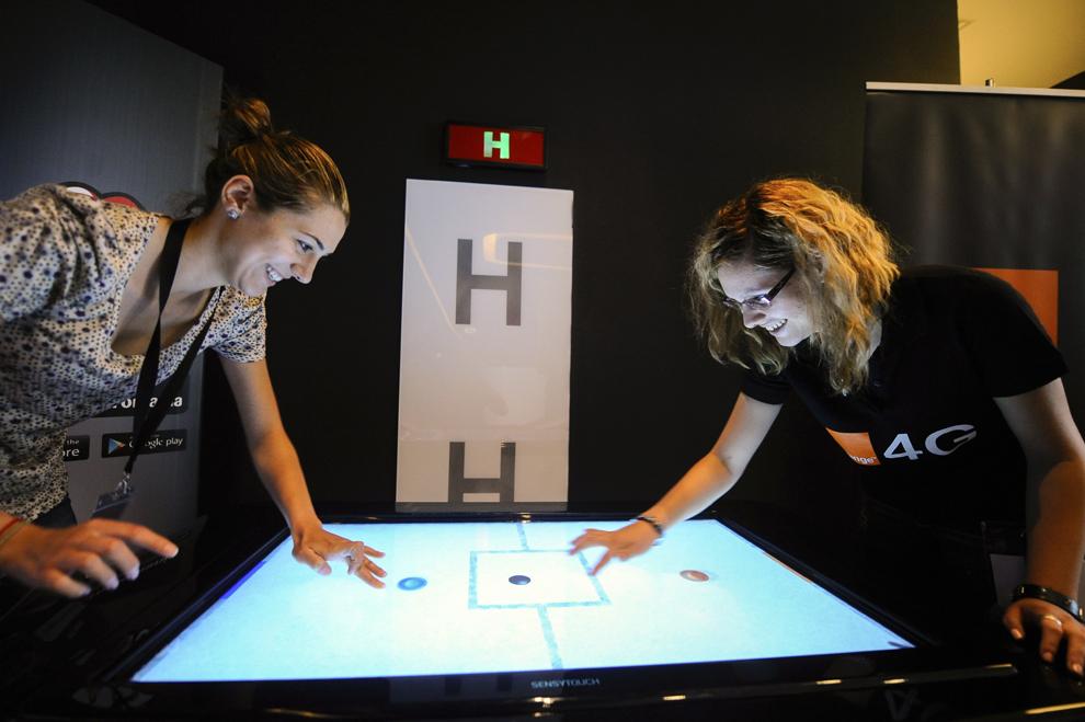 Două tinere se joacă pe o masă multi-touchscreen, în timpul festivalului dedicat industriei digitale şi interactive din Europa Centrală şi de Est, Interactive Central and Eastern Europe Festival 2014 (ICEEFest), în Bucureşti, joi, 12 iunie 2014.