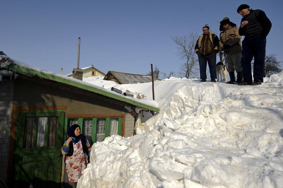 O femeie reacţionează în timp ce discută cu un grup de vecini în satul Vânători, comuna Petrachioaia, Ilfov, vineri, 10 februarie 2012.