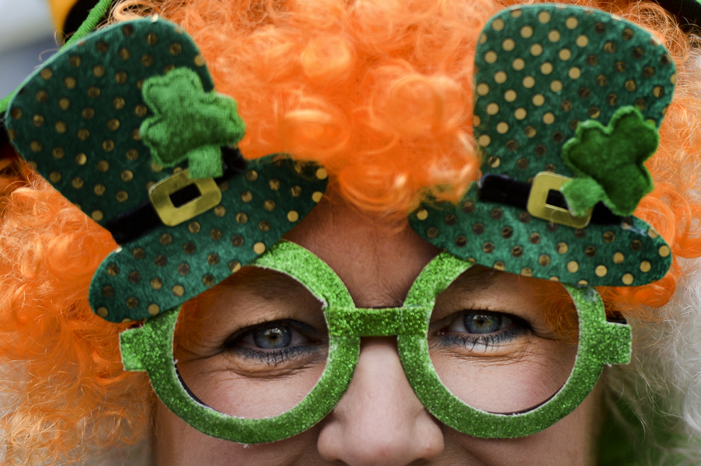 O femeie pozează cu o pereche de ochelari ornaţi cu trifoi, în timpul paradei de Sf. Patrick, organizate de Ambasada Irlandei cu ocazia Zilei Naţionale a Irlandei, în Bucureşti, duminică, 17 martie 2013.