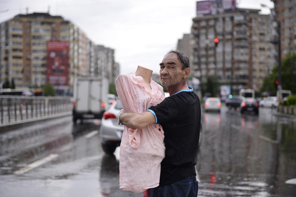 Un comerciant îşi duce produsele afectate de vijelie, după ce standul său s-a prabuşit din cauza unei furtuni, în zona Baba Novac din Bucureşti, joi, 23 mai 2013.