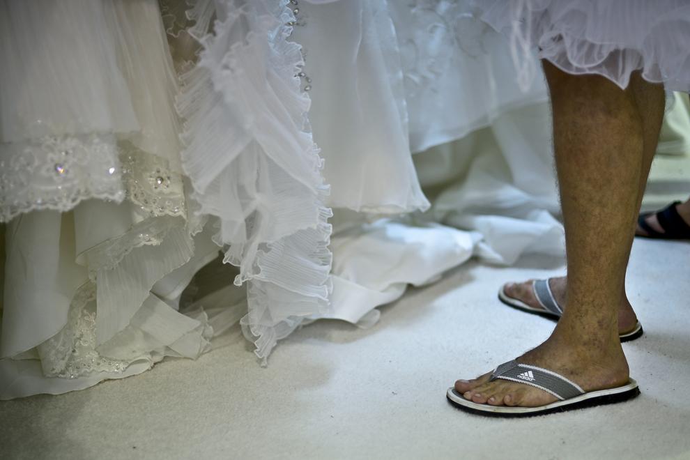 """Picioarele unui bărbat pot fi văzute lângă trenele mai multor rochii de mireasa, în timpul unui eveniment de tip """"black friday"""", în Bucureşti, vineri, 5 iulie 2013."""