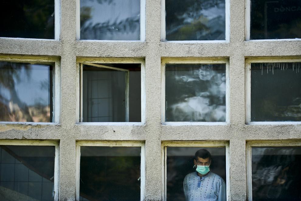 """Un pacient, cu o mască medicală pe faţă, priveşte de la geamul unei secţii a Institutului de Pneumoftiziologie """"Marius Nasta"""", în Bucureşti, luni, 2 septembrie 2013."""