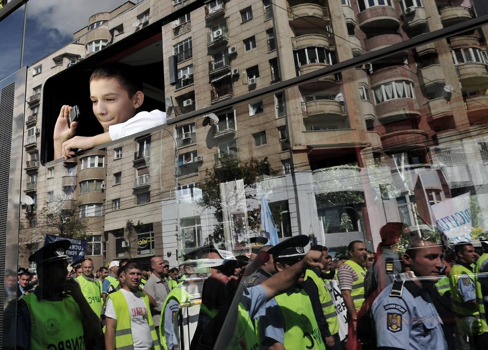 Un copil fotografiază cu telefonul mobil protestatari ce se reflectă într-o fereastra de autobuz, în timpul unui protest, vineri, 24 septembrie 2010.