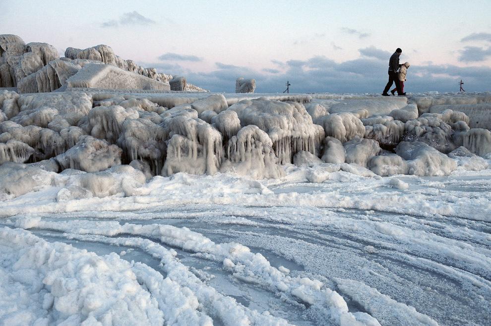 Un bărbat merge pe faleza îngheţată a Mării Negre, în oraşul Constanţa, miercuri, 1 februarie 2012.