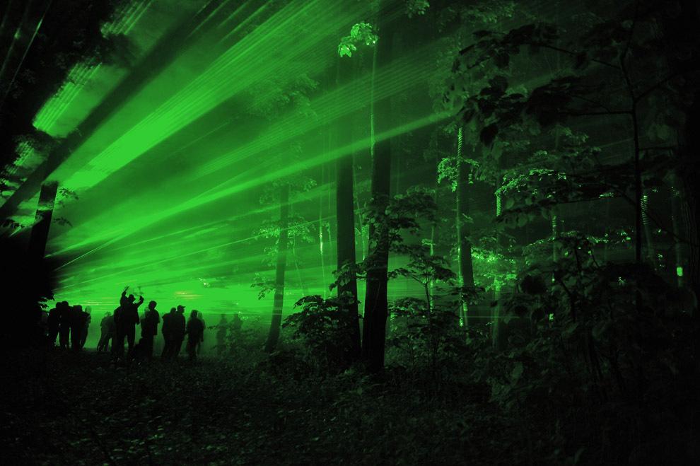 Persoane dansează într-o pădure iluminată de lasere, în timpul unei petreceri cu lasere, în Baloteşti, sâmbătă, 14 mai 2011.