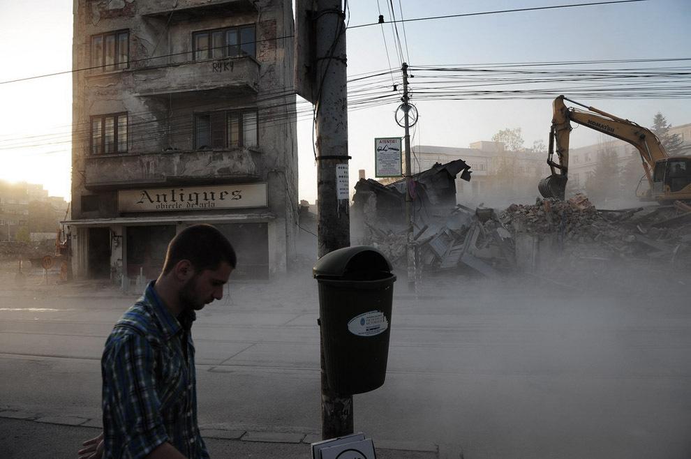 Un bărbat trece pe lângă un şantier al unei clădiri aflate în demolare pe strada Buzeşti din Bucureşti, marţi, 15 noiembrie 2011.