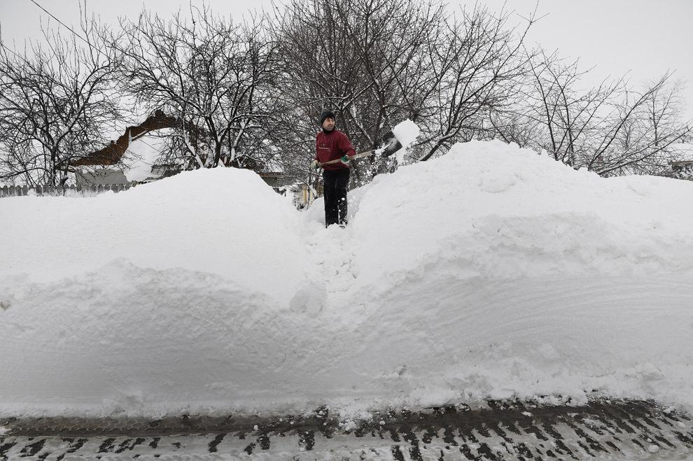 Un bărbat curăţă de zăpadă intrarea în casa sa din satul Smeeni, aflat la aproximativ 100 de km de Bucureşti, marţi, 28 ianuarie 2014.