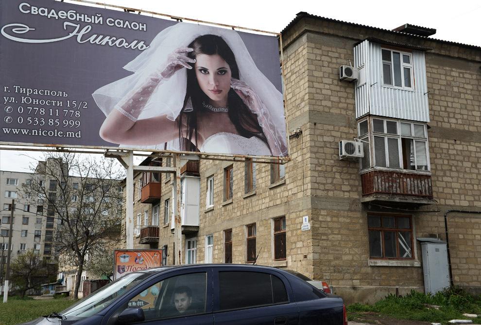 Un bărbat conduce un autoturism prin faţa unui panou stradal ce face reclamă unui restaurant de nunţi, în Tiraspol, Transnistria, miercuri, 16 aprilie 2014.