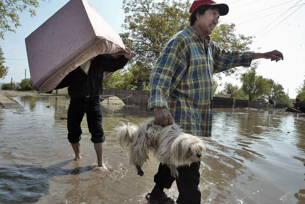 Localnici îşi părăsesc casele, în timpul unei inundaţii în satul Spantov, aflat la aproximativ 100 de km sud de Bucureşti, marţi, 25 aprilie 2006.