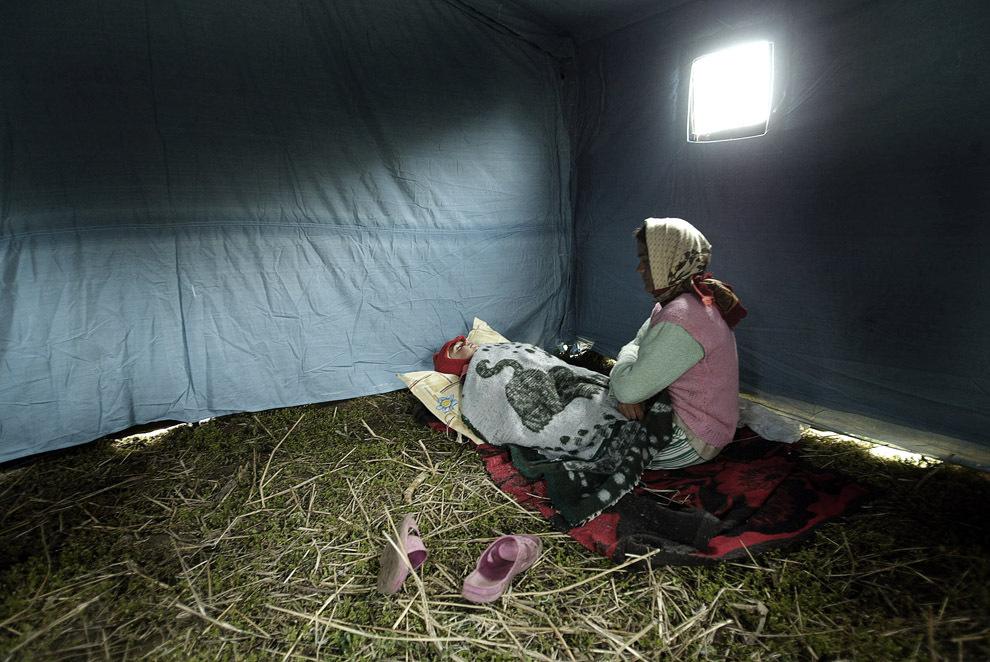 O femeie îşi leagănă copilul, într-un cort militar aflat într-o tabără improvizată în urma unor inundaţii puternice în satul Chiselet, aflat la aproximativ 100 de km sud de Bucureşti, marţi, 25 aprilie 2006.
