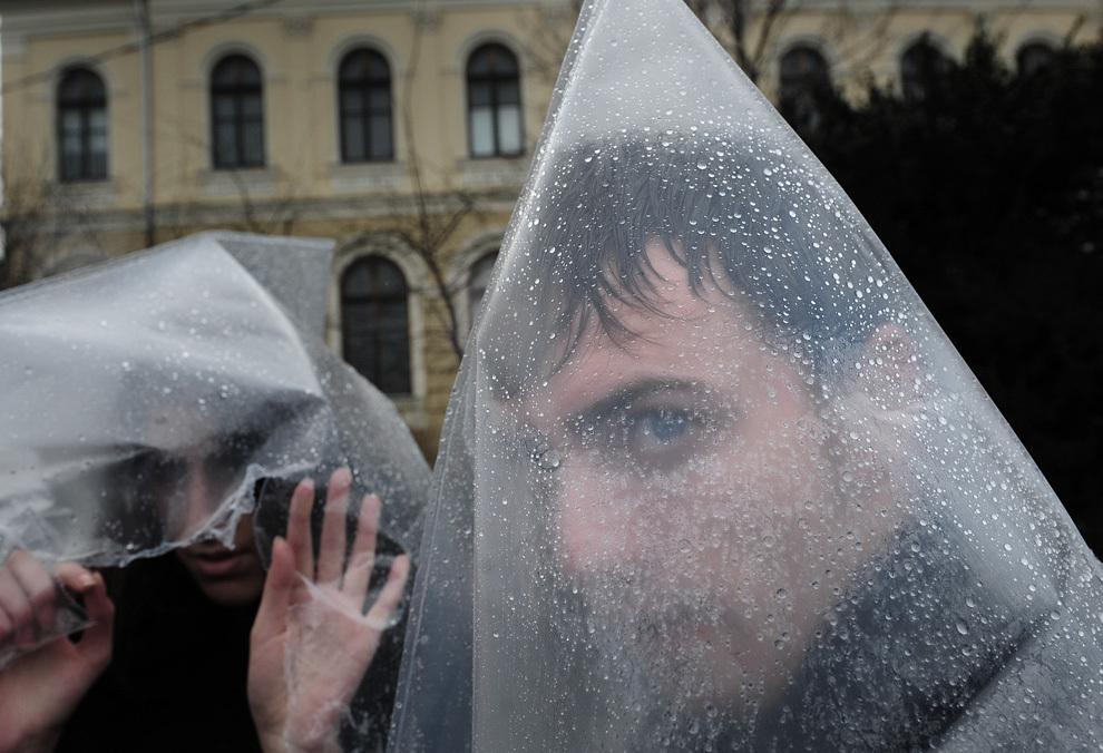 Tineri de etnie romă se protejează de ploaie în timpul unui protest, desfăşurat în faţa Guvernului României, miercuri, 24 februarie 2010.
