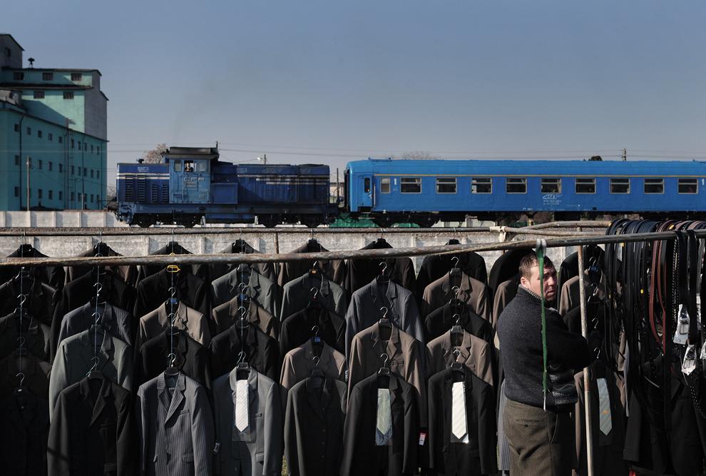 Un bărbat îşi aranjează marfa expusă, în timp ce un tren trece prin apropiere, într-o piaţă din Roşiori de Vede, aflata la 100 de km de Bucureşti, vineri, 19 martie 2010.