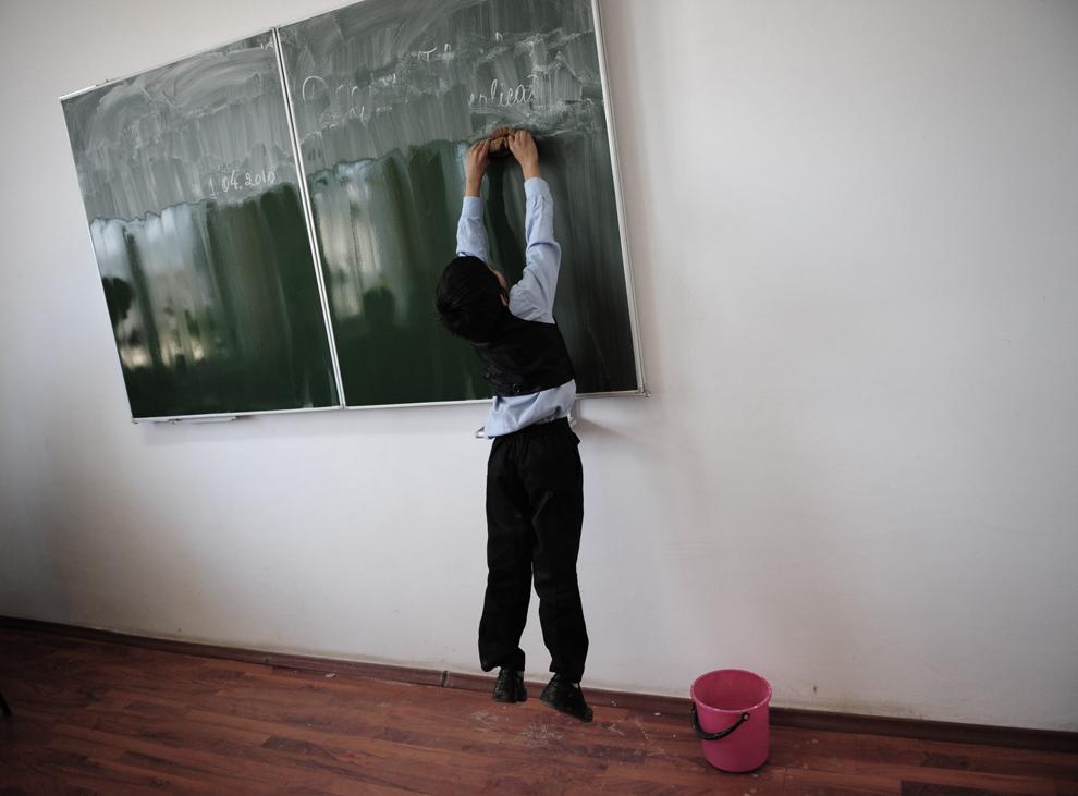 Un copil curăţă cu buretele tabla unei săli de curs, într-o şcoală mixtă de români şi romi, în satul Dârvari, aflat la 30 de km de Bucureşti, joi, 1 aprilie 2010.