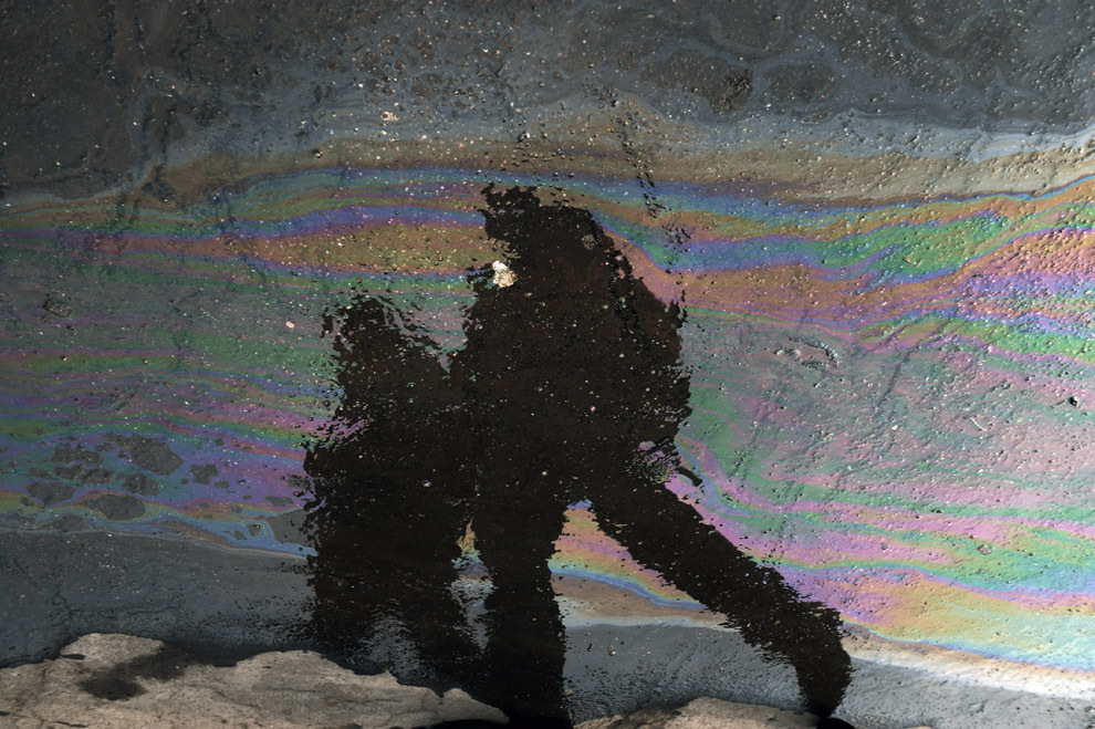 Pietoni se reflectă pe o peliculă de ulei, în Bucureşti, joi, 3 martie 2011.