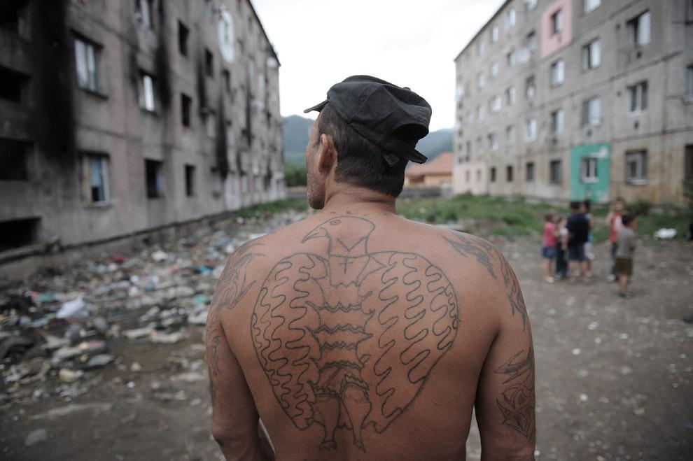 Un bărbat tatuat stă într-o curte interioară a unui cartier de blocuri de apartamente, în Baia Mare, joi, 21 iulie 2011.