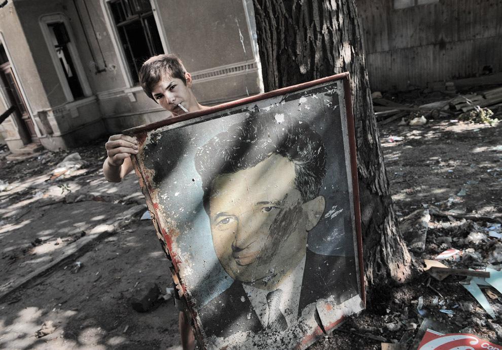Un tânăr ţine în mână un portret al dictatorului român, Nicolae Ceauşescu, în timp ce colectează resturi ce urmează a fi vândute, dintr-o casă ce urmează a fi demolată, în Bucureşti, duminică, 21 august 2011.