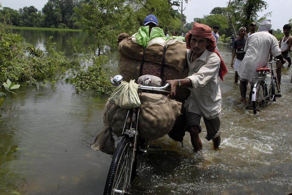 Localnicii trec pe o şosea inundată din localitatea Katol, satul Bihar, India, duminică, 26 august 2007. Statul Bihar, aflat în nordul Indiei, a fost cel mai afectat de inundaţiile cauzate de anotimpul musonic.