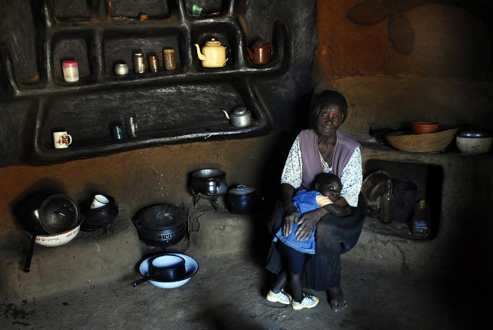 Lily Dube şi strănepoata ei. Lily a fost profesoară în sat. Întreaga colibă e făcută şi decorată cu mâna ei. Satul Makwe, Zimbabwe, marţi, 13 iulie 2010.