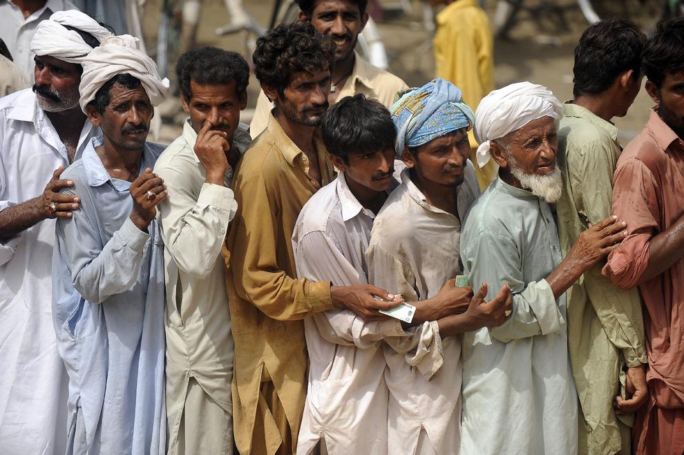 """Pakistanezi stau la coadă pentru a primi ajutoare, aduse de Fundaţia pentru Protecţia Animalelor """"Vier Pfoten"""", în satul Basti Saray din districtul Layyah, duminică, 29 august 2010. Vier Pfoten a împărţit, în mai multe sate afectate de inundaţiile din Pakistan, furaje pentru hrana a 10.000 de animale domestice."""