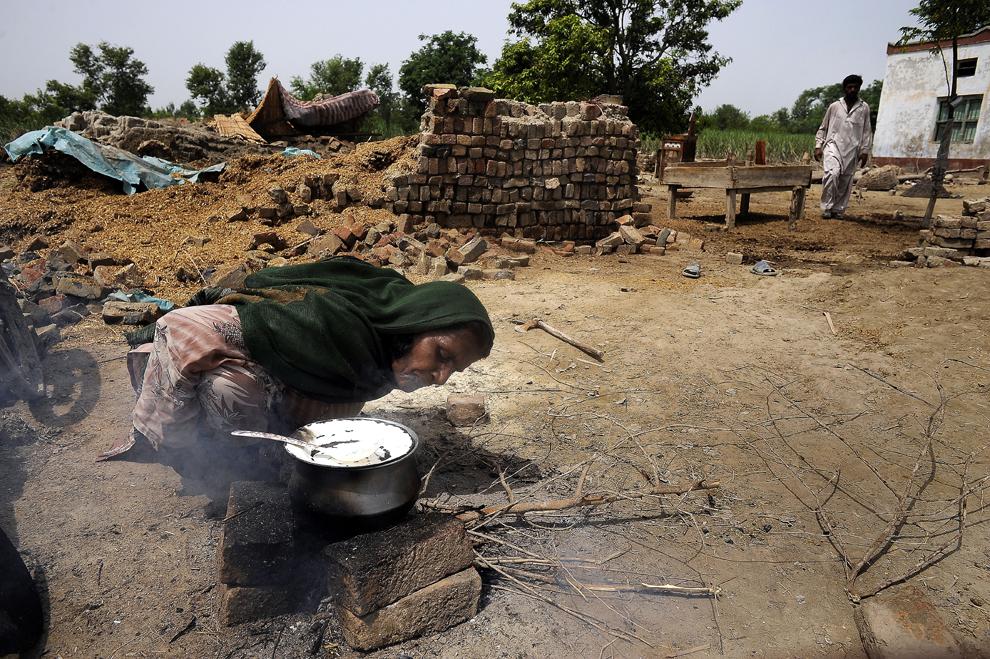 O femeie găteşte în curtea sa din satul Shado Khan, districtul Layyah, duminică, 28 august 2010. Ploile torenţiale musonice au declanşat inundaţii, considerate a fi cel mai mare dezastru natural care a lovit vreodată Pakistanul, afectând peste 17 milioane de oameni.