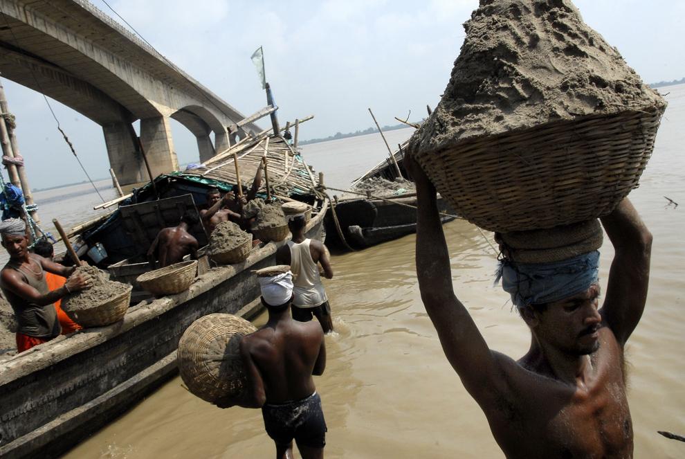 Muncitori zilieri descarcă nisip din barci, lângă podul Mahatma Gandhi Setu din Patna, capitala statului Bihar, marţi, 4 septembrie 2007.