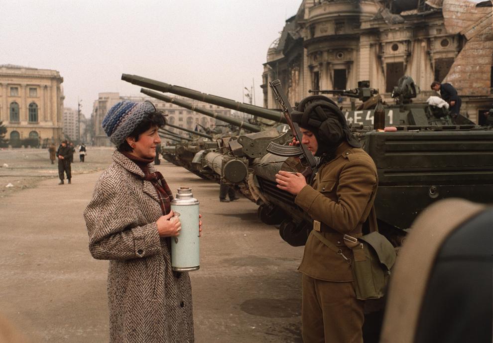 O femeie oferă o băutură fierbinte unui soldat român care păzeşte clădirea Securităţii, în Bucureşti, luni, 25 decembrie 1989.