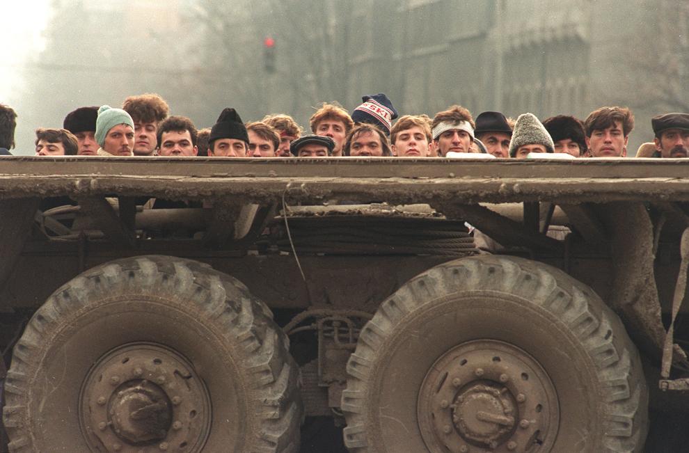 Oameni privesc luptele desfăşurate în timpul Revoluţiei Române, feriţi de un camion, în Bucureşti, duminică, 24 decembrie 1989.