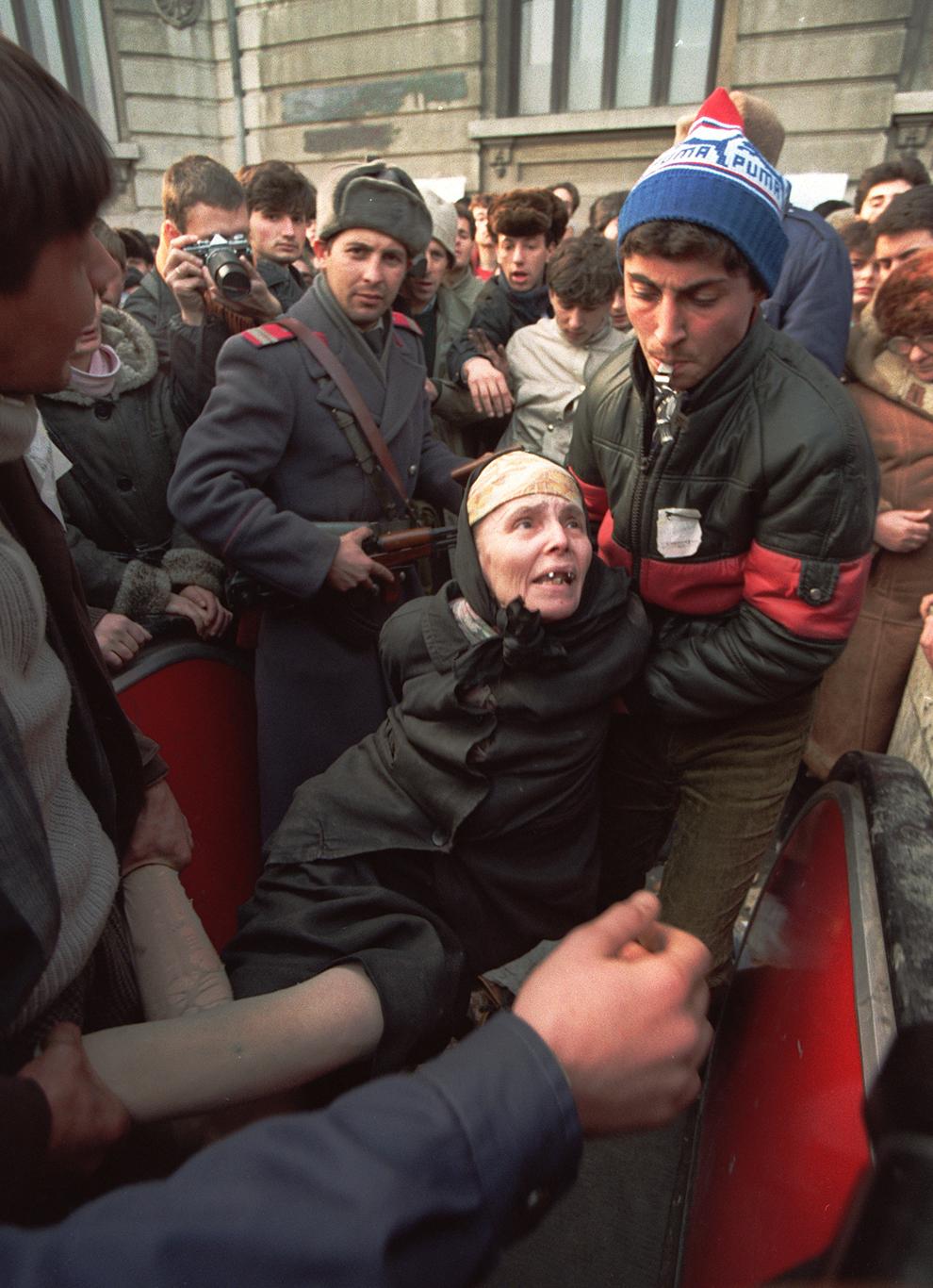O femeie este ţinută de un bărbat, după ce i s-a descoperit dinamită în geantă, în Bucureşti, luni, 25 decembrie 1989.