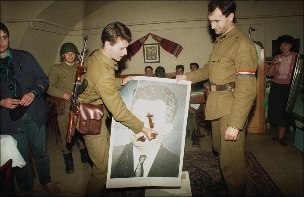 Un militar înfige o baionetă în portretul lui Nicolae Ceauşescu, în timpul Revoluţiei Române, în Sibiu, luni, 25 decembrie 1989.