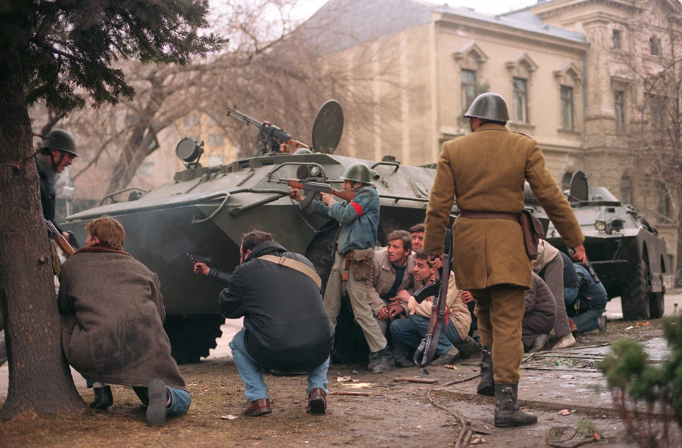 Un grup de luptători civili, împreună cu un militar, se feresc în spatele unui transportor blindat, în timpul Revoluţiei Române, duminică, 24 decembrie 1989.