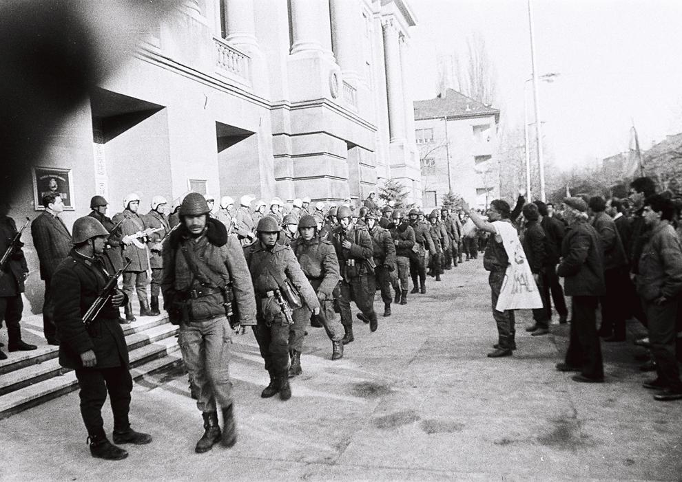 """Militari păzesc intrarea în Prefectura din Timişoara. Revoluţionarii strigă """"Fără gloanţe"""" şi """"Fără violenţă"""" miercuri, 20 decembrie 1989."""
