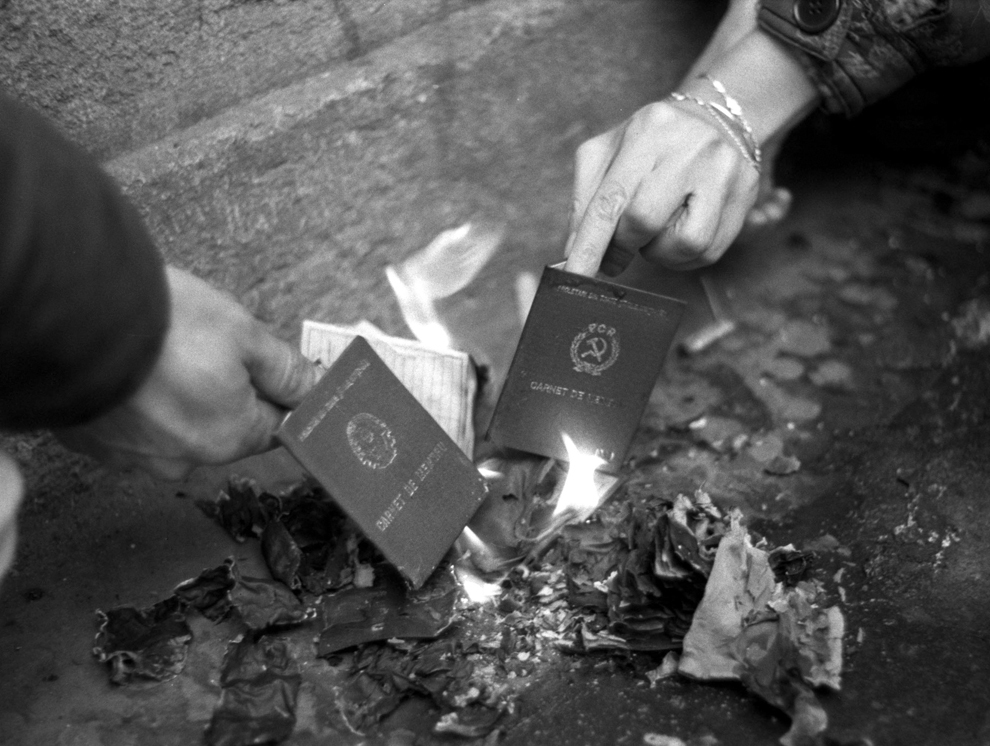 Două persoane ard carnete de membru al PCR, în Bucureşti, în timpul evenimentelor din decembrie 1989.