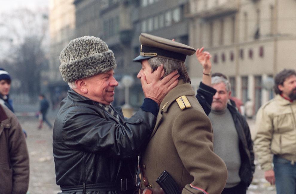 Un civil şi un ofiţer al armatei române se îmbrăţişează pe o stradă din Timişoara, luni, 25 decembrie 1989.