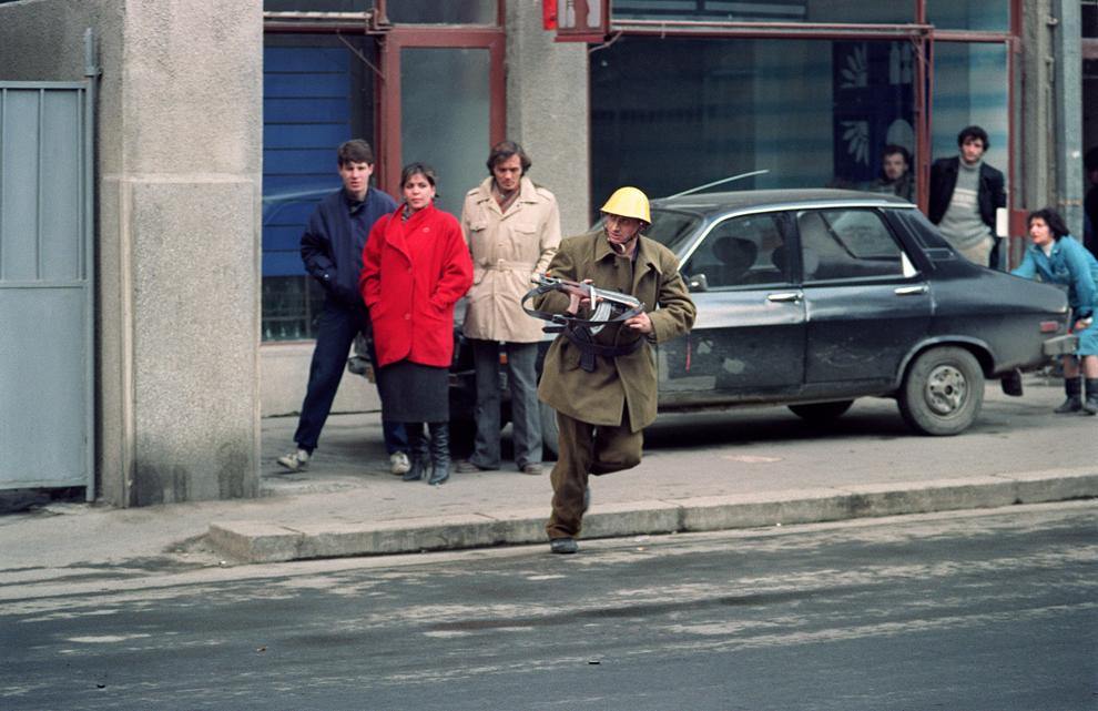 Un soldat român, care ţine o puşcă automată, traversează o stradă din Bucureşti, marţi, 26 decembrie 1989.