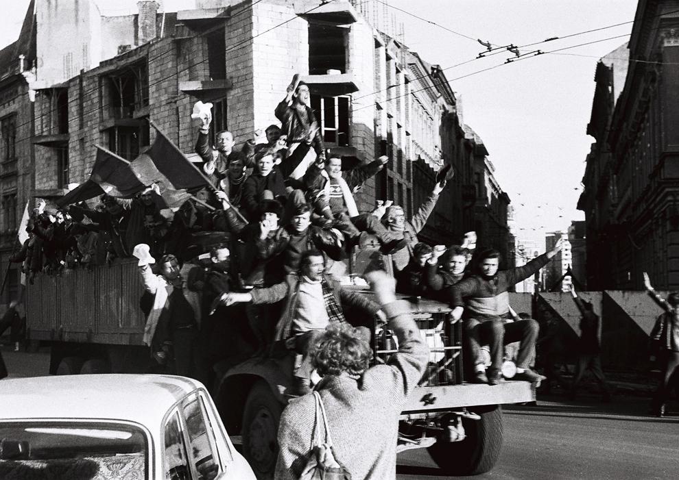 """Manifestanţi urcaţi pe o maşină strigă """"Libertate"""" şi """"Jos Ceauşescu"""", în Timişoara, miercuri, 20 decembrie 1989."""