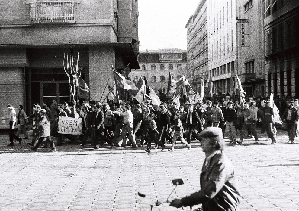 Un muncitor trece pe motoretă prin faţa demonstranţilor care cer democraţie, în Timişoara, miercuri, 20 decembrie 1989.