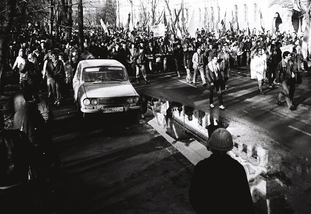 Muncitori de la fabricile Electromotor şi Elba merg spre Primărie purtând steagul României fără stemă şi strigând lozinci anticomuniste, în Timişoara, miercuri, 20 decembrie 1989.