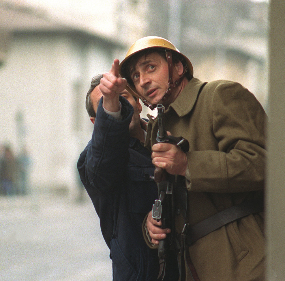 Un bărbat discută cu un soldat care ţine în mâini o armă, în Bucureşti, marţi, 26 decembrie 1989.