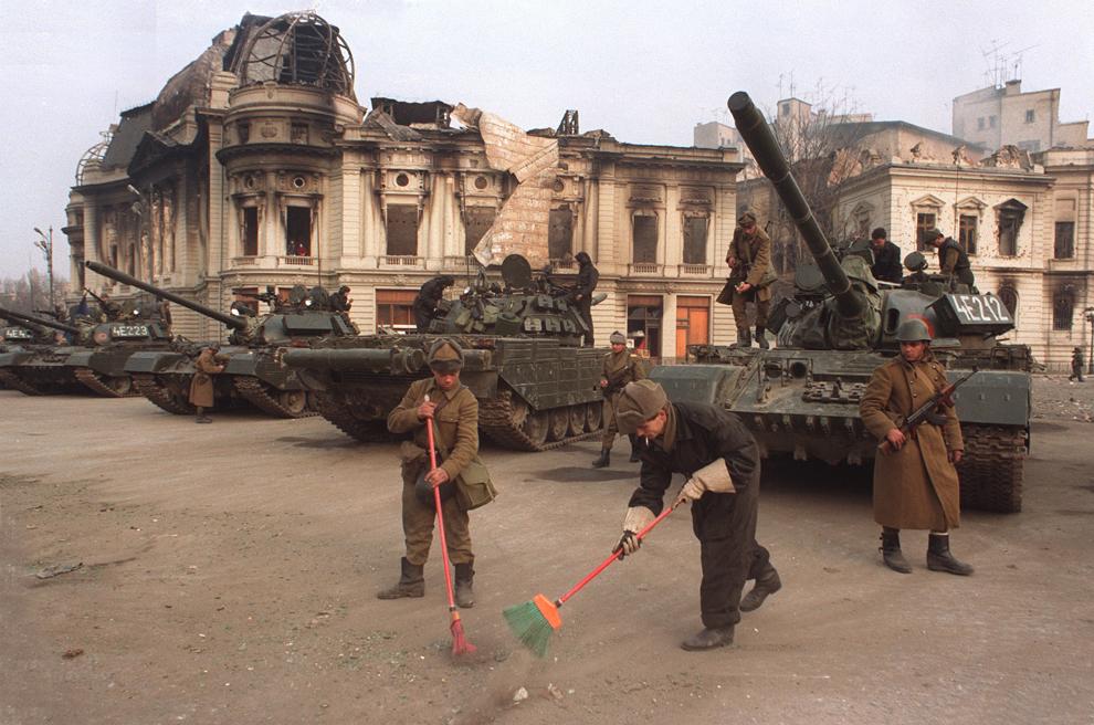 Soldaţi ai Armatei Române mătură în faţa tancurilor, marţi, 26 decembrie 1989.