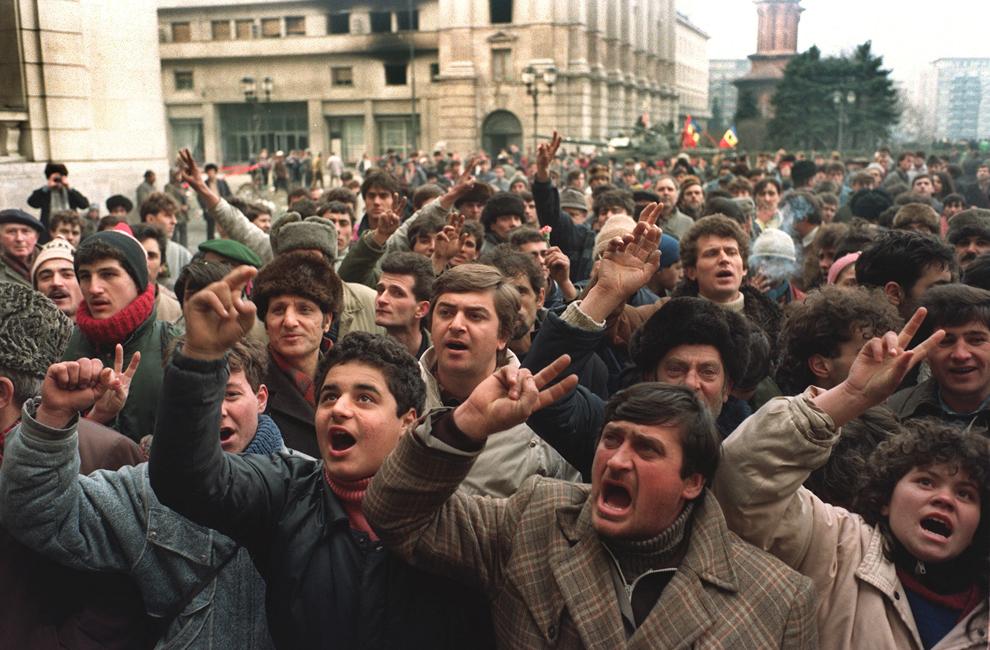 Oameni sunt adunaţi în faţa sediului Comitetului Central al Partidului Comunist Român, cerând un nou guvern după executarea fostului lider Nicolae Ceauşescu şi a soţiei sale Elena, în Bucureşti, marţi, 26 decembrie 1989.