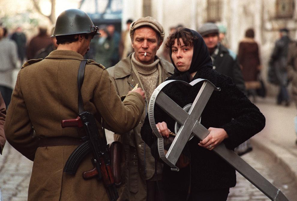 O femeie care ţine o cruce pentru mormântul soţului ei, ucis în Revoluţia Română, este verificată de către soldaţi, în Timişoara, joi, 28 decembrie 1989.