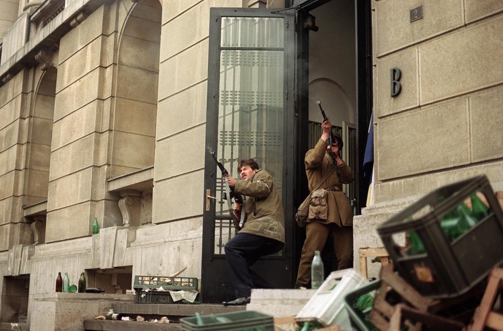 Un militar al Armatei Române şi un civil luptă împreună, în timpul Revoluţiei Române, în Bucureşti, duminică, 24 decembrie 1989.
