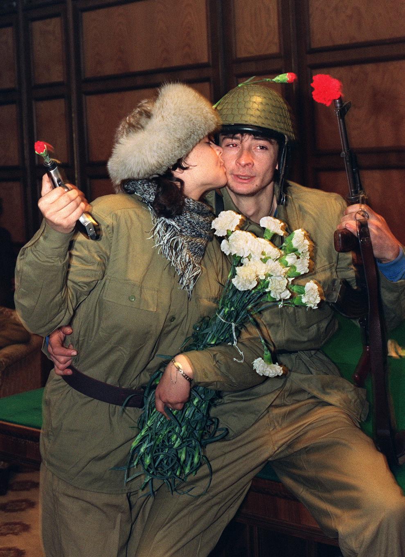 O femeie soldat, cu un pistol în mână, sărută un militar al Armatei Române, înarmat cu un Kalachnikov AK-47, în timpul Revoluţiei Române, miercuri, 27 decembrie 1989.